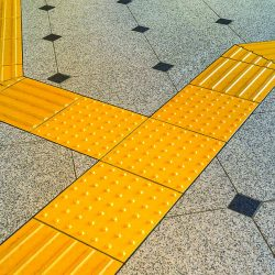 Sidewalk guides for blind. Yellow concrete cobblestones on walkway for blindness people